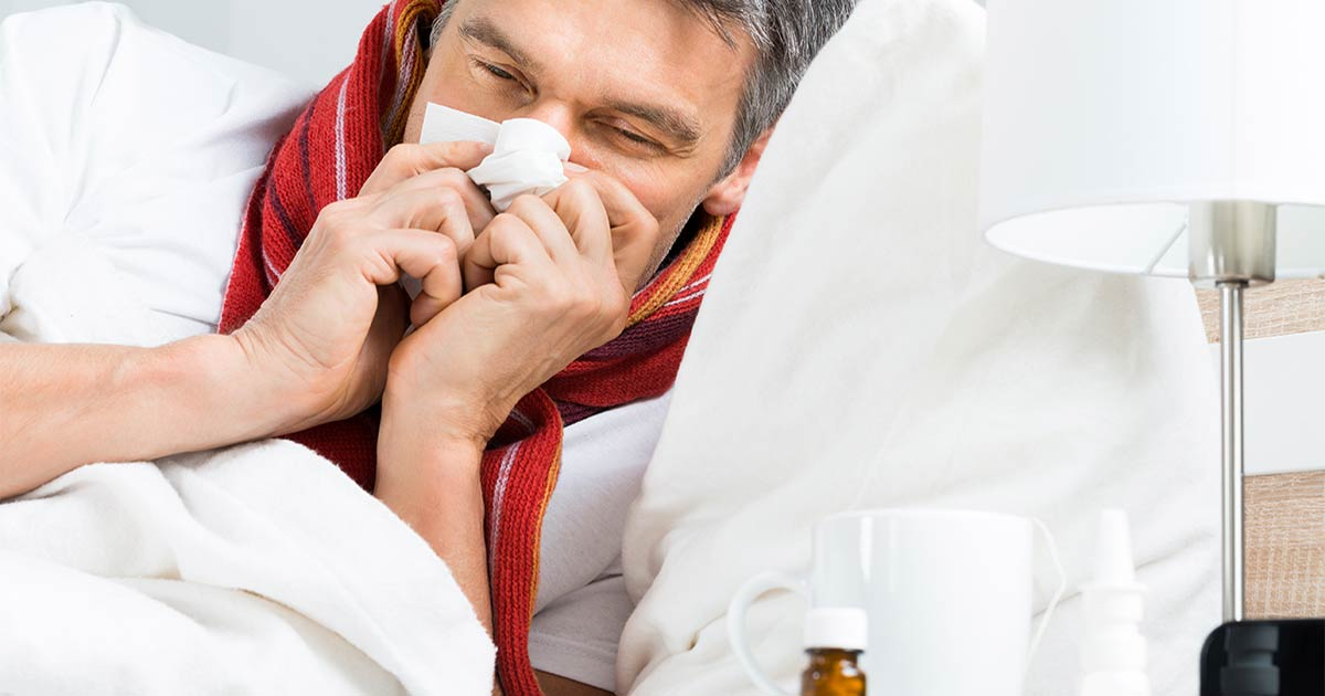 man sneezing at home with flu