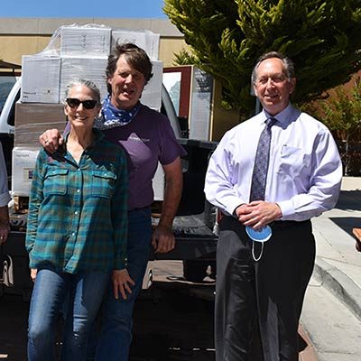 LVMC staff standing with wine makers and their truck load of donated wine