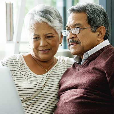 older latino couple looking at laptop