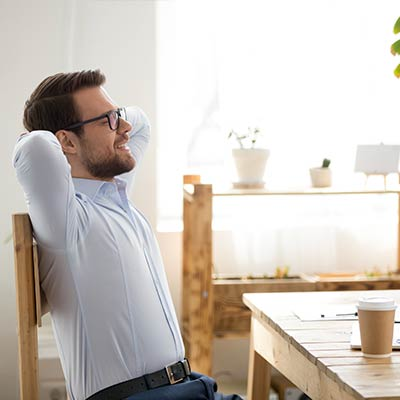 Man stretching while siting in front of laptop