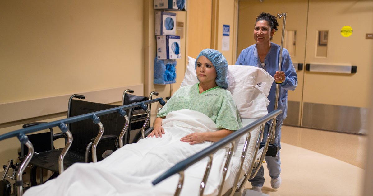nurse moving patient out of surgery